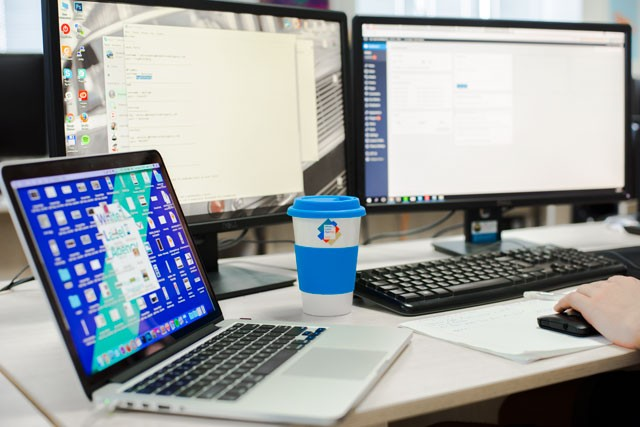 White Label Agency's developer's desk set up with screens, MacBook and a coffee cup